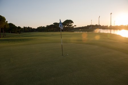 achivement: golf ball on edge of course hole representing achivement and success business concept, beautiful sunset in background