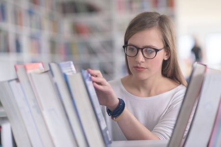 famale: portrait of smart looking famale student girl  in collage school library,  selecting book to read from bookshelf Stock Photo