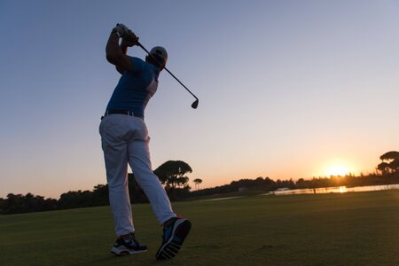 plan �loign�: golfer hitting long shot with driver on course at beautiful sunset Banque d'images