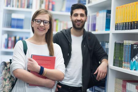 hombre arabe: feliz grupo de estudiantes en la biblioteca de la escuela de seleccionar libros para leer y caminar