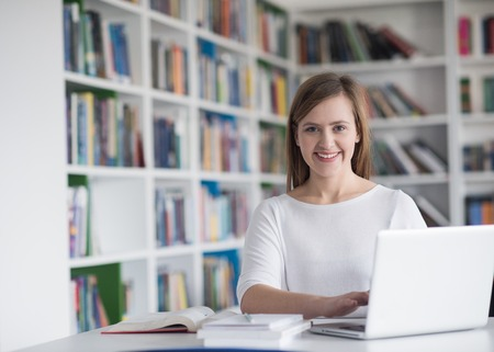 internet school: female student study in school library, using laptop and searching for informations on internet