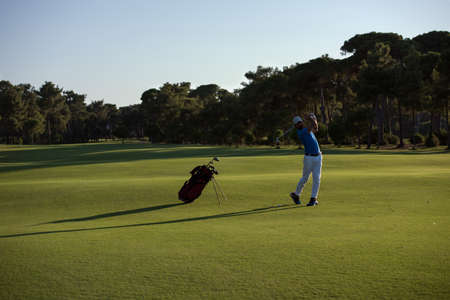 long shot: golfer hitting long shot with driver on course at beautiful sunset Stock Photo