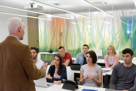 science class: group of students study with professor in modern school classroom