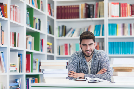 hard to find: Portrait of happy student while reading book in school library. Study lessons for  exam. Hard worker and persistance concept.