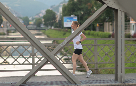blonde woman: sporty woman running on sidewalk at early morning with city  sunrise scene in background Stock Photo