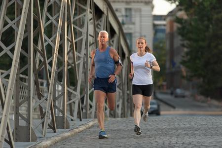 バック グラウンドで日の出と早朝に街でジョギング健康的な熟女カップル