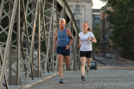 healthy mature couple jogging in the city  at early morning with sunrise in background Stock Photo - 60898663