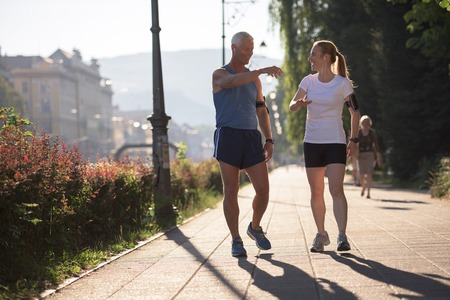 playlist: jogging couple check music playlist on phone and plan route before morning running workout  with sunrise in the city  and sun flare in background