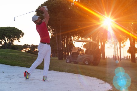 ploy: golf player shot ball from sand bunker at course with beautiful sunset with sun flare