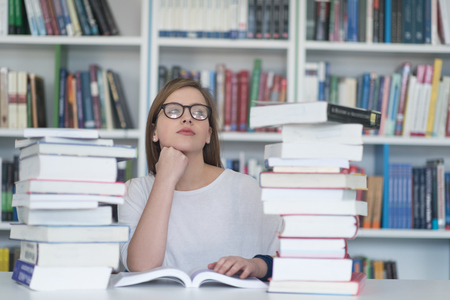 internet school: female student study in school library, using tablet and searching for information�s on internet. Listening music and lessons on white headphones Stock Photo