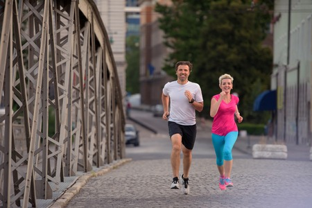 healthy mature couple jogging in the city  at early morning with sunrise in background Stock Photo - 60899076