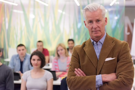 the elderly tutor: portrait of confident teacher,  students group in background
