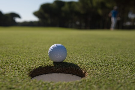achivement: golf ball on edge of course hole representing achivement and success business concept