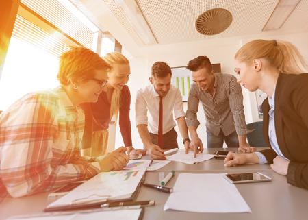 para iniciar una empresa joven grupo de personas creativas de intercambio de ideas sobre la reunión en la oficina usando la computadora portátil y el ordenador tableta tener en cuenta planes de ideas y proyectos amanecer o al atardecer con el sol bengala en el fondo
