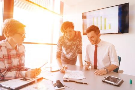 groupe de jeunes gens créatifs de démarrage d'entreprise de brainstorming sur la réunion au bureau en utilisant un ordinateur portable et une tablette pour noter des plans d'idées et des projets de lever ou de coucher du soleil avec des reflets de soleil en arrière-plan