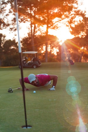 cheating: golf player blowing ball in hole. concept of cheating and success, beautiful sunset in backgrund