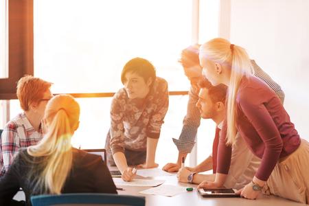 para iniciar una empresa joven grupo de personas creativas de intercambio de ideas sobre la reunión en la oficina usando la computadora portátil y el ordenador tableta tener en cuenta planes de ideas y proyectos amanecer o al atardecer con el sol bengala en el fondo Foto de archivo