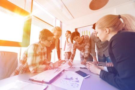 entreprise démarrage groupe de jeunes gens créatifs de remue-méninges sur la satisfaction au bureau utilisant un ordinateur portable et ordinateur tablette de noter des idées plans et projets lever ou le coucher du soleil avec le soleil flare en arrière-plan