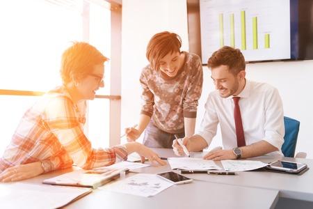 スタートアップ ビジネス創造的な若者はラップトップを使用してオフィスでの会議でブレーンストーミングをグループ化し、タブレット コンピューターのアイデア計画とプロジェクト日の出や夕日背景に太陽フレアに注意するには 写真素材