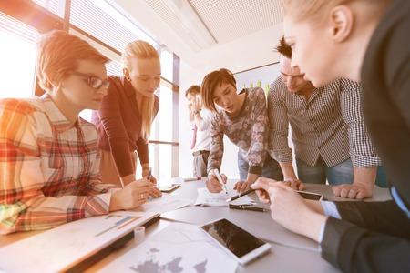 startup zakelijke jonge creatieve mensen groep brainstormen over de vergadering op kantoor met behulp van laptop en tablet-computer op te merken ideeën plannen en projecten zonsopgang of zonsondergang met zon flare op achtergrond