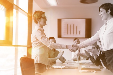 businesswomans handshake on team meeting  with group of people blured in background at modern startup business office interior photo