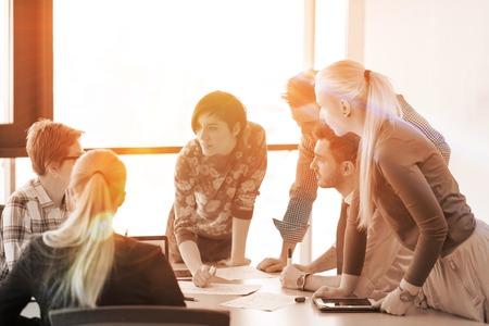 백그라운드에서 태양 플레어 아이디어 계획 및 일출 프로젝트 또는 일몰을주의하는 노트북 및 태블릿 컴퓨터를 사용하는 사무실에서 회의에 브레인