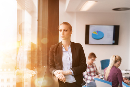 casual office: portrait of young business woman at modern startup office interior team in meeting group in background