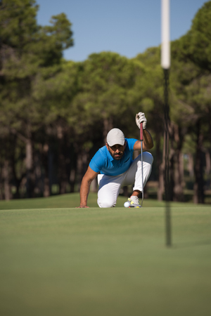 aim: golf player aiming shot with club on course at beautiful sunny day