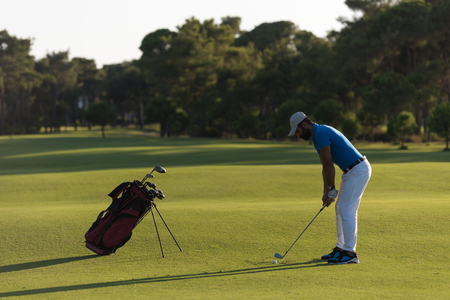 Golfista que golpea a largo tiro con conductor en el camino al atardecer hermoso