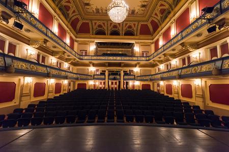 Sipario del teatro vuoto con le luci drammatiche Archivio Fotografico - 64140397