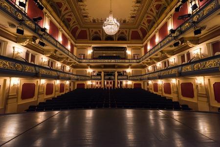 Sipario del teatro vuoto con le luci drammatiche Archivio Fotografico - 64142067