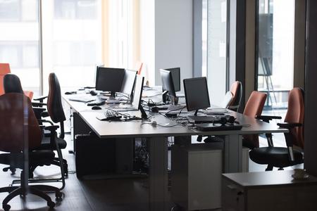 現代コンピューターおよびデュアル モニターの画面と空のスタートアップのオフィスのインテリア