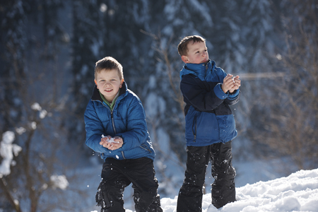 boys playing: happy kids playing in fresh snow at beautiful  sunny winter day