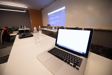 it: empty it classroom with program code on projector screen and modern laptop computers on table