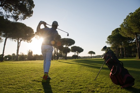 golf player hitting shot with driver on course at beautiful sunny day Banco de Imagens