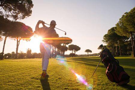 El jugador de golf que golpea un disparo con conductor en curso en hermoso día soleado
