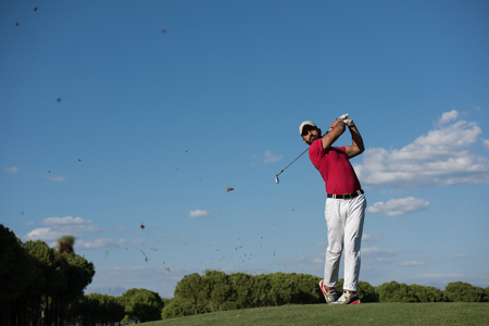shot: golf player hitting shot with driver on course at beautiful sunny day Stock Photo