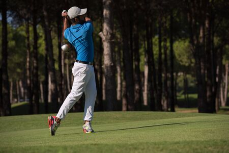 golf player hitting shot with driver on course at beautiful sunny day Stock Photo