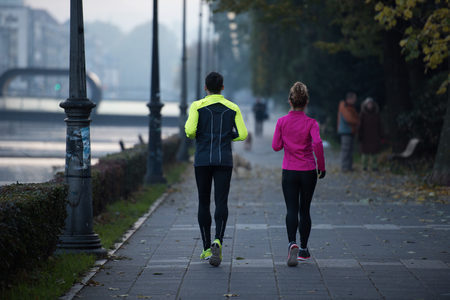 health and fitness: healthy young  couple jogging in the city  at early morning with sunrise in background Stock Photo