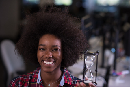 portrait of a young successful African American beautiful woman who enjoys spending a quality and joyful time while working in a large modern office Imagens