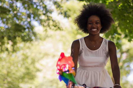 beautiful black woman: beautiful young African American women enjoy while riding a bicycle in the woods on a sunny summer day Stock Photo