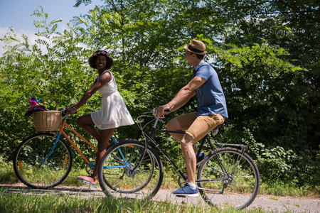young happy couple: a young man and a beautiful African American girl enjoying a bike ride in nature on a sunny summer day