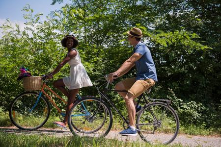 jovenes felices: un joven y una hermosa niña afroamericana disfrutar de un paseo en bicicleta en la naturaleza en un día soleado de verano