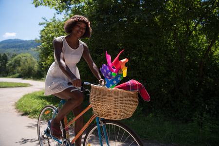 young women: beautiful young African American women enjoy while riding a bicycle in the woods on a sunny summer day Stock Photo