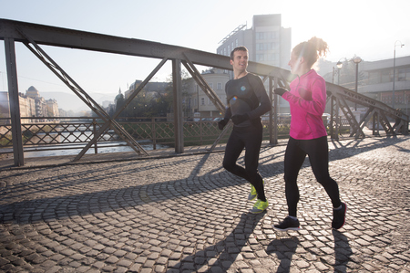 couple outdoor: healthy young  couple jogging in the city  at early morning with sunrise in background Stock Photo