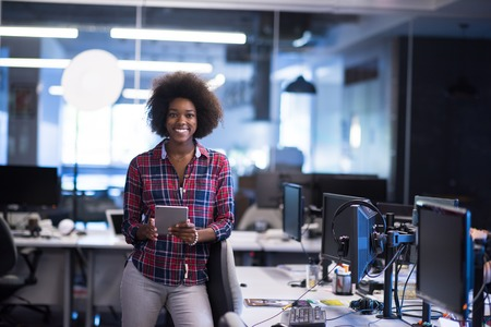 happy work: portrait of a young successful African American beautiful woman who enjoys spending a quality and joyful time while working in a large modern office Stock Photo