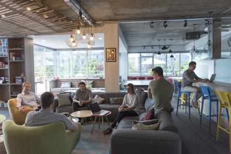 노트북에 작업 및 커피를 마시는 동안 현대 사무실에서 젊은 사람들의 그룹 팀 회의 및 브레인 스토밍을 스톡 콘텐츠
