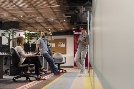 近代的なオフィスにカジュアルな若者グループ会議やブレーンストーミングとして毎日仕事彼らのチームがあります。