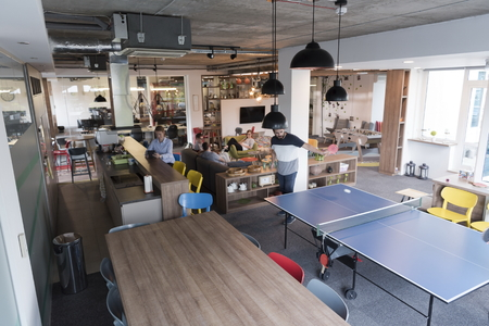 mid thirties: Two young start up business man playing table tennis at modern creative office space  people group have meeting and brainstorming in background