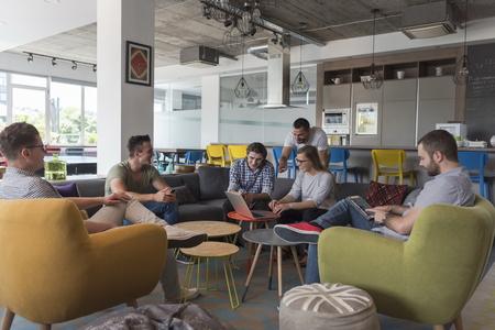 Gruppe der jungen Leute in der modernen Büro-Team Treffen und Brainstorming während der Arbeit am Laptop und Kaffee zu trinken Standard-Bild